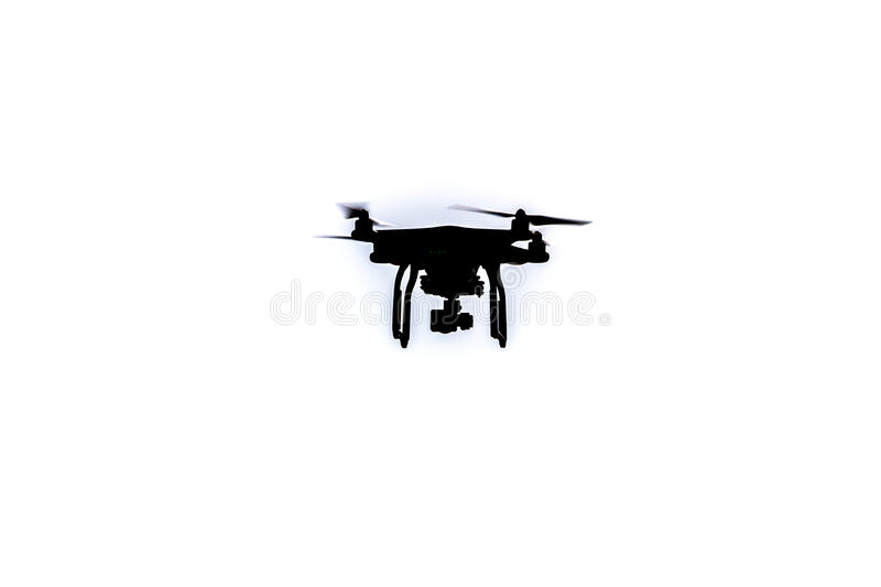 Black Drone hovering in a bright blue sky stock image
