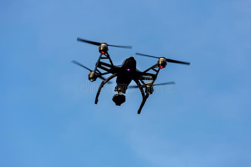 Black drone quadcopter with camera flying over blue sky. Angle view royalty free stock image
