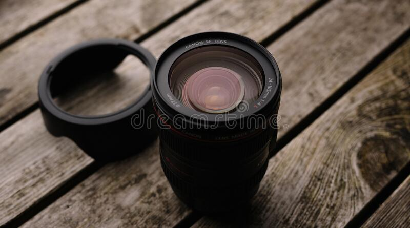 Black Dslr Camera Lens With Lid on Wooden Platform royalty free stock photo