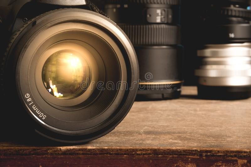 Black DSLR camera with 50mm 1.8G prime lens on an old brown wooden vintage box surface. Close up of a black DSLR camera with 50mm 1.8G prime lens on an old brown stock photo