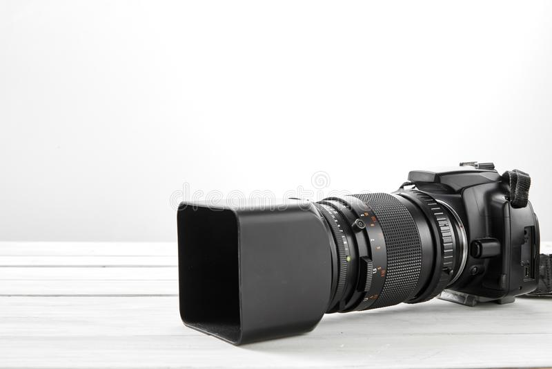 BLACK DSLR Camera with tele lens. OLD Digital photo BLACK DSLR camera tele lens on white wooden background royalty free stock photo