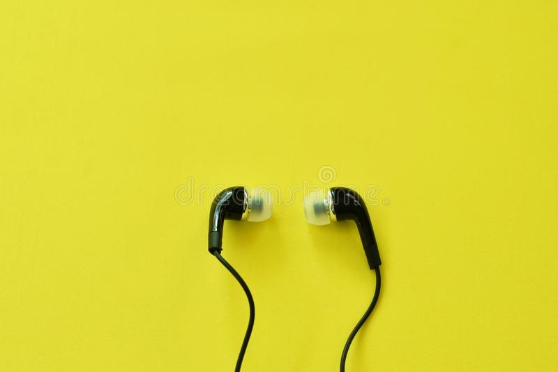 Black earphone for connecting with mobile phon arranging on yellow foam board background. Black earphone for connecting with mobile phon arranging on the yellow royalty free stock image
