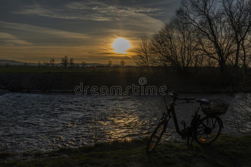 Black electric bicycle with sunset near weir on Malse river stock photos