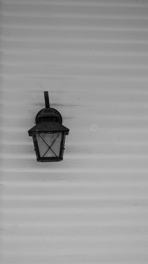 Black electric lamp styled after vintage gas street lamps, against a white exterior building wall of horizontal wood slats. Black electric lamp styled after royalty free stock photo