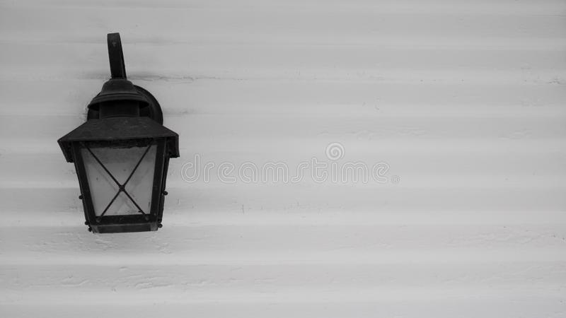 Black electric lamp styled after vintage gas street lamps, against a white exterior building wall of horizontal wood slats. Black electric lamp styled after stock image