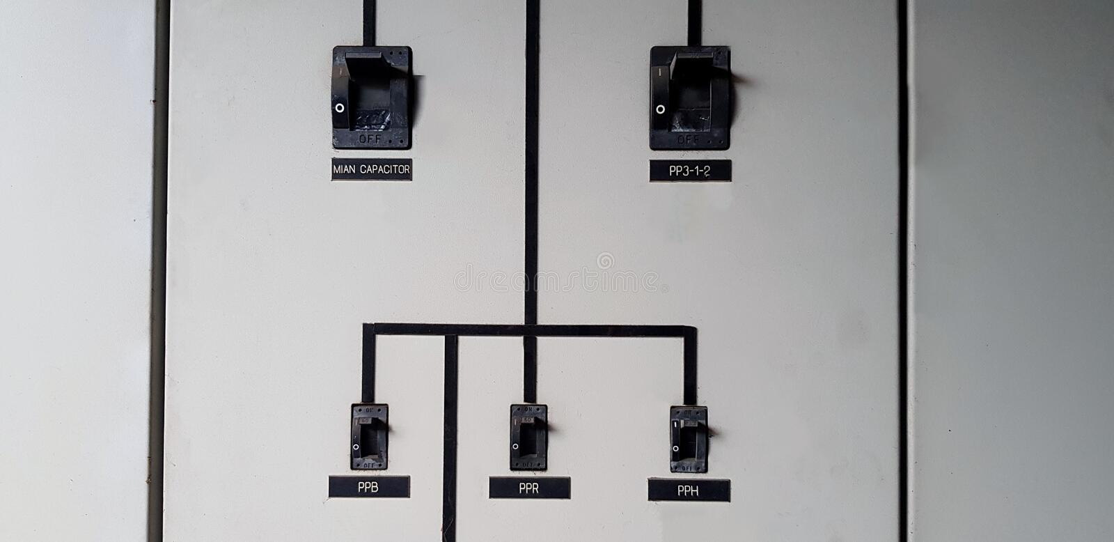 Black electrical main breaker connect with small switch on gray or grey stainless steel cabinet for distribution electric current. To switch or device with copy royalty free stock photo