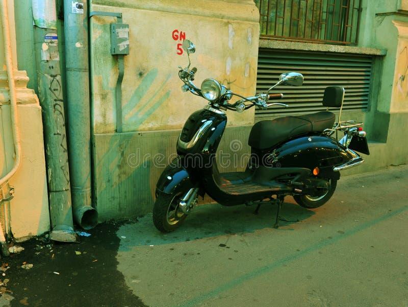 Black elegant scooter parked on the sidewalk royalty free stock photo
