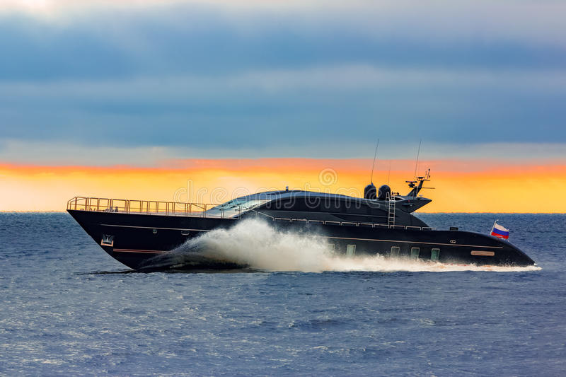 Black elite speed motor boat. Moving fast from Baltic sea stock photo