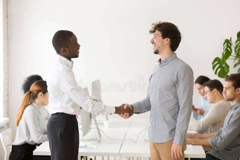 Black employer shaking hand of shy male Caucasian job applicant stock photo