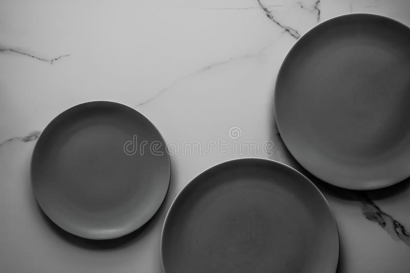 Serve the perfect plate. Black empty plate on marble, flatlay - stylish tableware, table decor and food menu concept. Serve the perfect dish stock photos