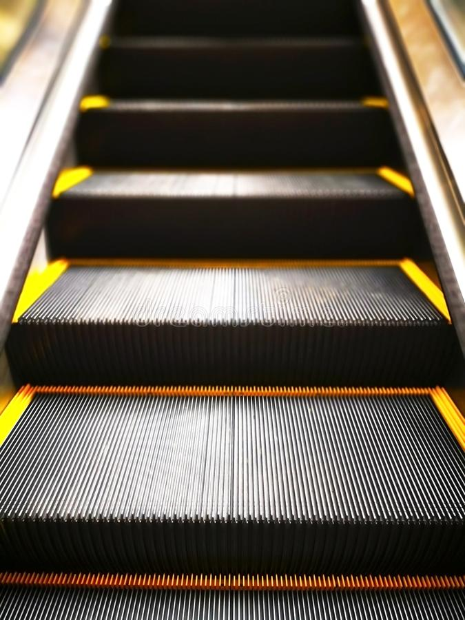 The black escalator with yellow edges, move into the higher floor. Concept, people who are moving forward towards a better life. royalty free stock photo