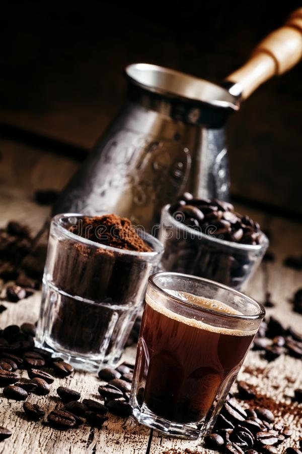 Black espresso coffee and ingredients for cooking: roasted coffee beans, ground coffee, Turkish coffee maker, vintage wooden back stock photos