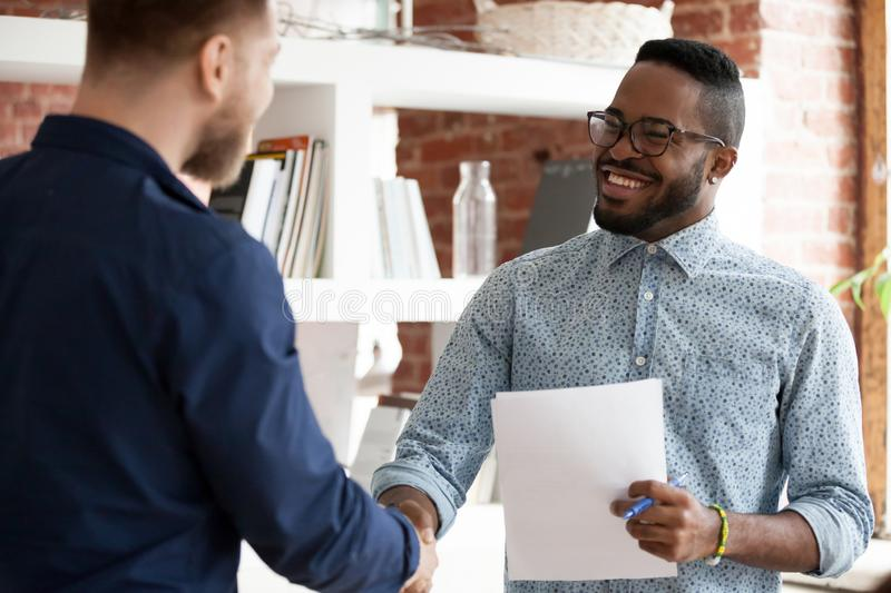 Black executive manager greeting company client starting business meeting. Mixed race executive company ceo shaking hands with client during business royalty free stock photos