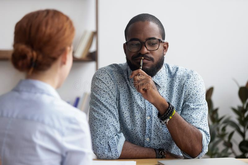 Black executive manager interviewing female for company position. Diverse business people sitting in office, black ceo interviewing female for company position stock photography