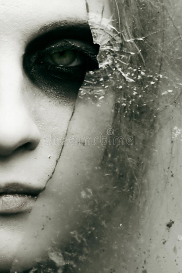 Black eye and broken glass. Partial view of a female face with heavy black eye makeup, surrounded by a broken pane of glass. Color desaturated stock photos