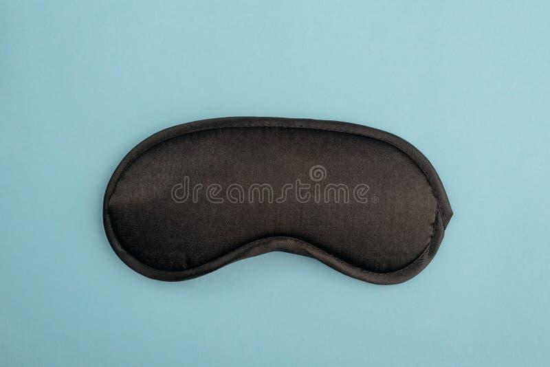Black eye mask on blue. Background. Stylish bedside accessory to block any light for a good sleep royalty free stock photo