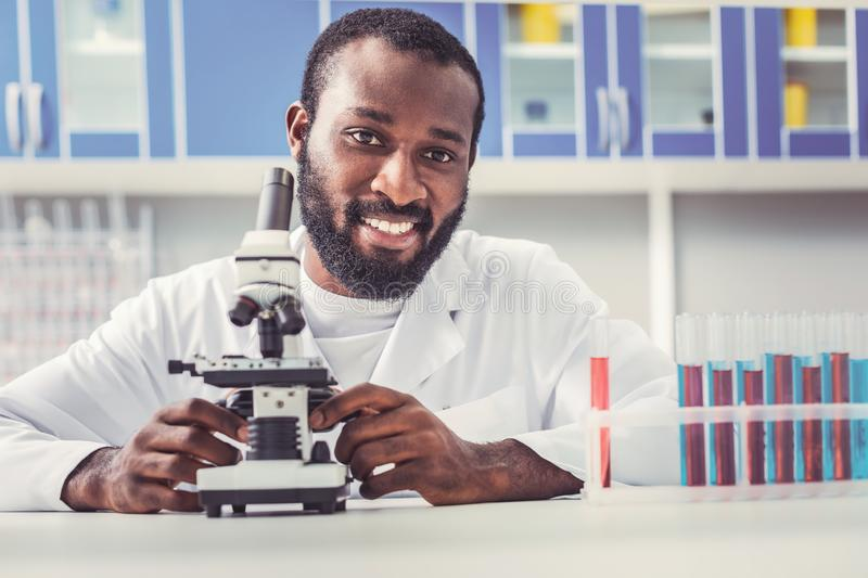 Black-eyed man working as chemist sitting near microscope. Black-eyed man working as chemist feeling inspired while sitting near modern microscope stock images
