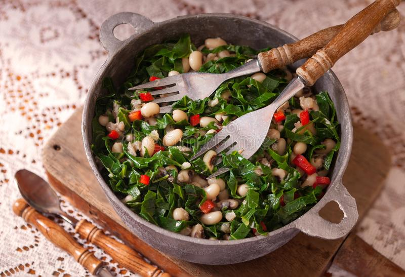 Black Eyed Peas and Collard Greens. High angle view of a USA southern New Year`s favorite dish of black eyed peas, collard greens and corn bread royalty free stock photos