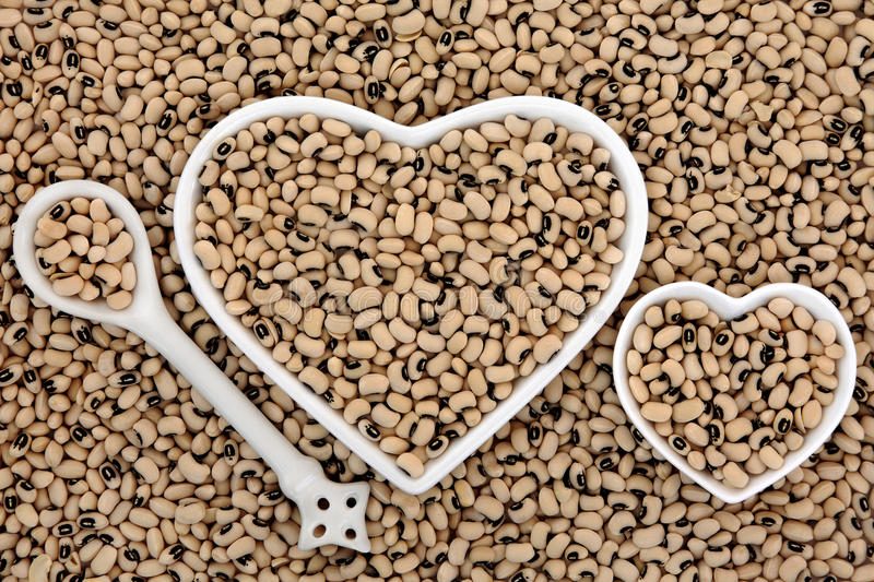 Black Eyed Peas. Health food in heart shaped bowls and porcelain spoon forming an abstract background stock image