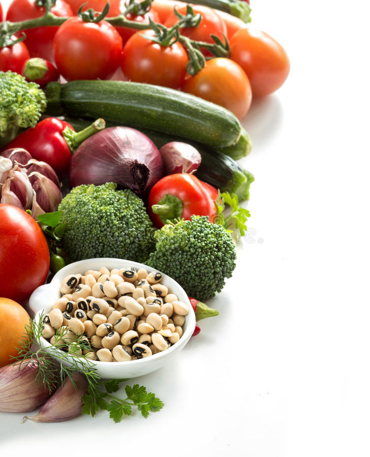 Black eyed peas and vegetables. Black eyed peas in a bowl and vegetables stock image