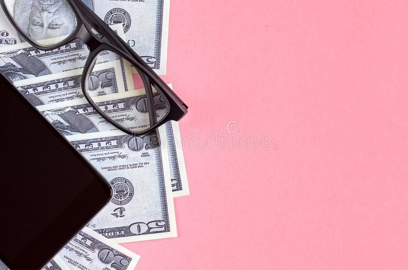 Black eyeglasses, cellphone and money on pink background composition stock photos