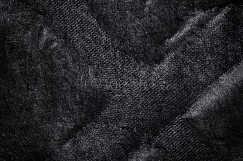 Black fabric canvas silk texture background. Abstract closeup detail of textile material wallpaper. X cross shape emboss. Cloth, shadow, dark, mesh, woven stock photography