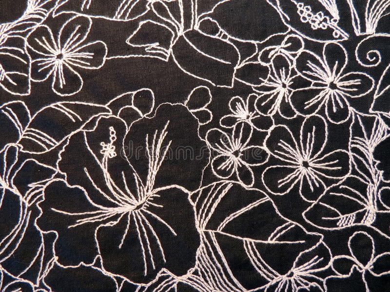 Black fabric texture. With white flowers ornaments stock photos