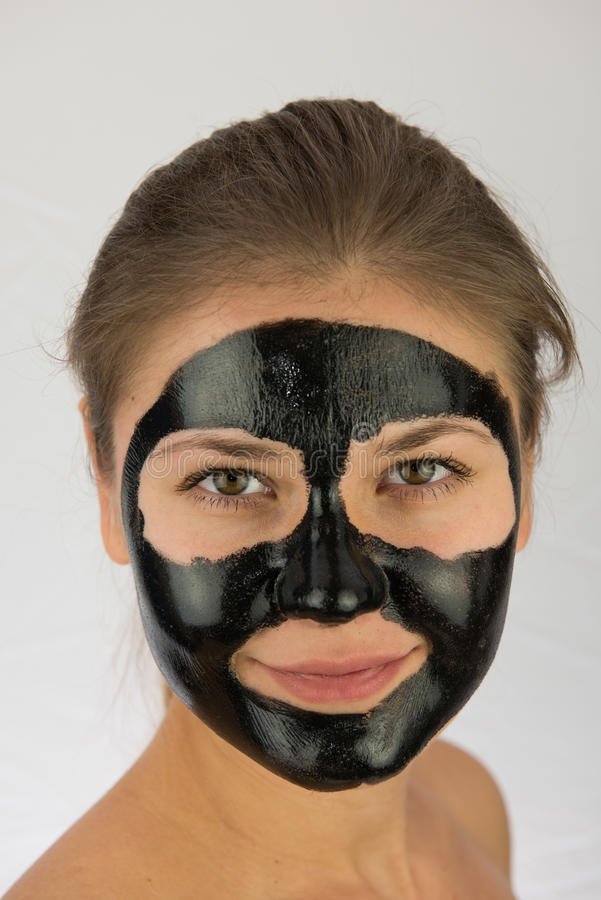 Black face mask. Young blond woman in black peeling face mask royalty free stock photo