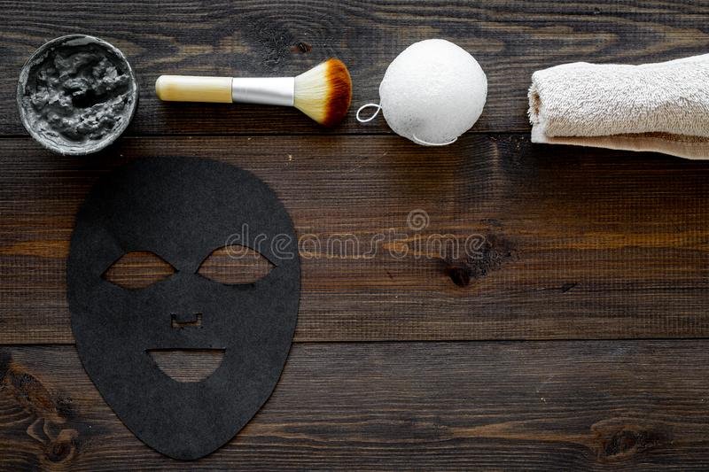 Black facial mask. Black head remover mask. Mask with clay on dark wooden background top view copy space. Black facial mask. Black head remover mask. Mask with royalty free stock photography