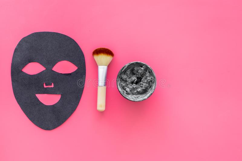 Black facial mask. Black head remover mask. Mask with clay on pink background top view copy space. Black facial mask. Black head remover mask. Mask with clay on stock image