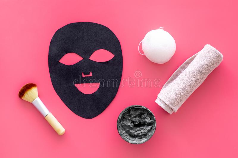 Black facial mask. Black head remover mask. Mask with clay on pink background top view.  stock photo