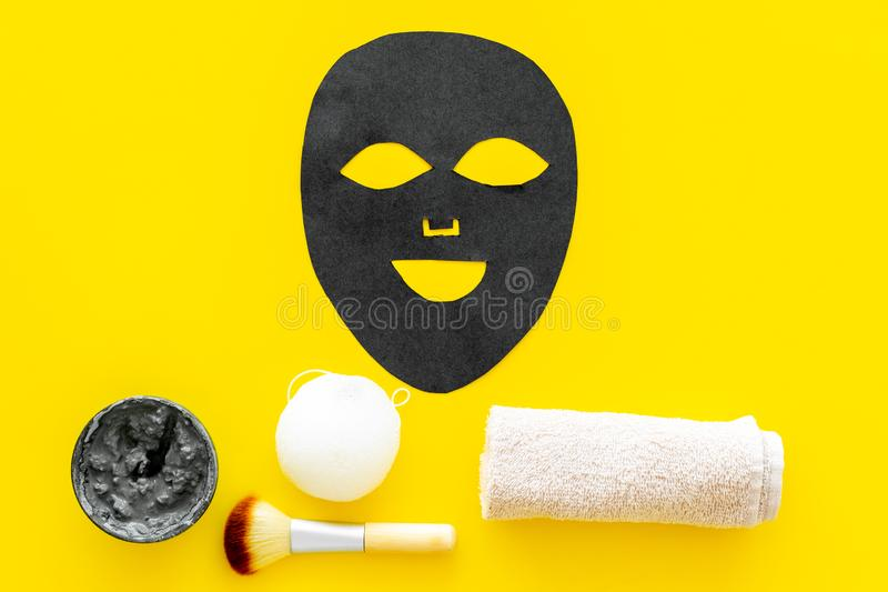 Black facial mask. Black head remover mask. Mask with clay on yellow background top view copy space. Black facial mask. Black head remover mask. Mask with clay royalty free stock photo