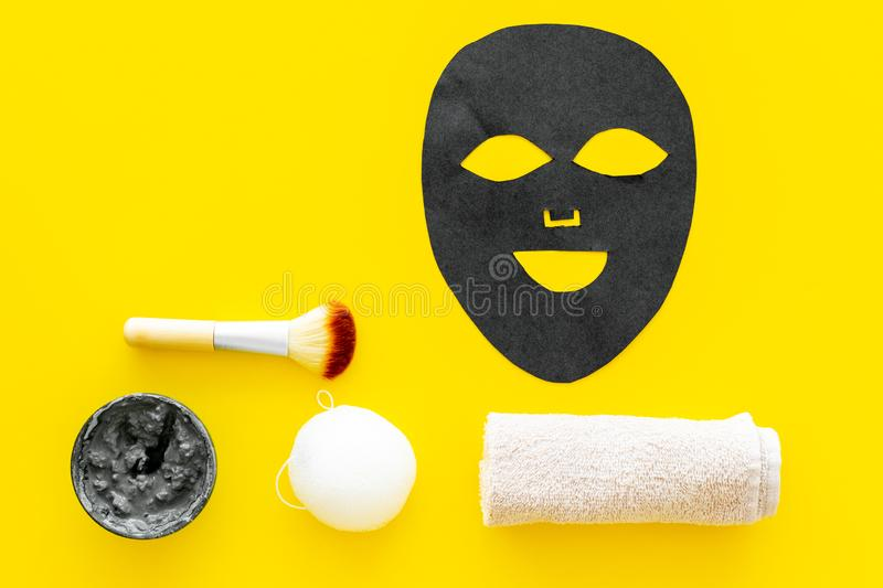 Black facial mask. Black head remover mask. Mask with clay on yellow background top view copy space. Black facial mask. Black head remover mask. Mask with clay stock photos