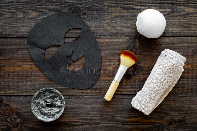 Black facial mask for face spa. Black head remover mask. Mask with clay on dark wooden background top view. Black facial mask for skin care. Black head remover stock photography