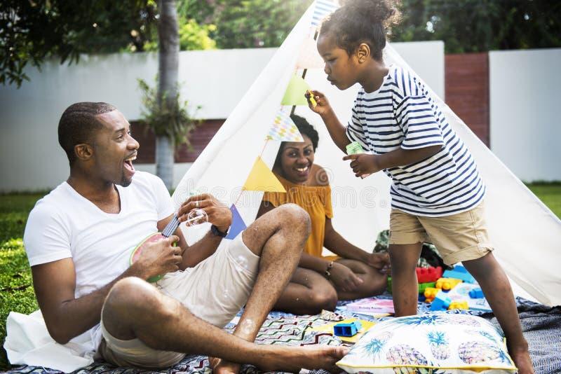 Black family enjoying summer together at backyard blowing soap b. Ubbles royalty free stock photos