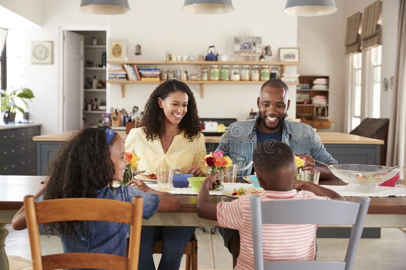 Black family of four having lunch in their kitchen at home stock image