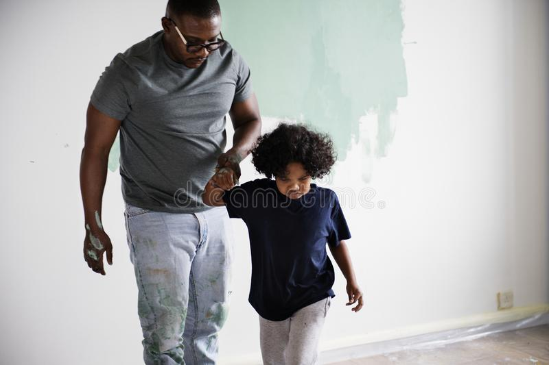 Black family painting house wall together stock photo