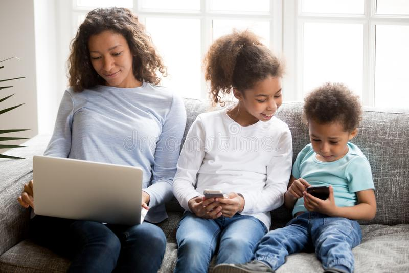 Mother and two kids together with gadgets on couch stock images