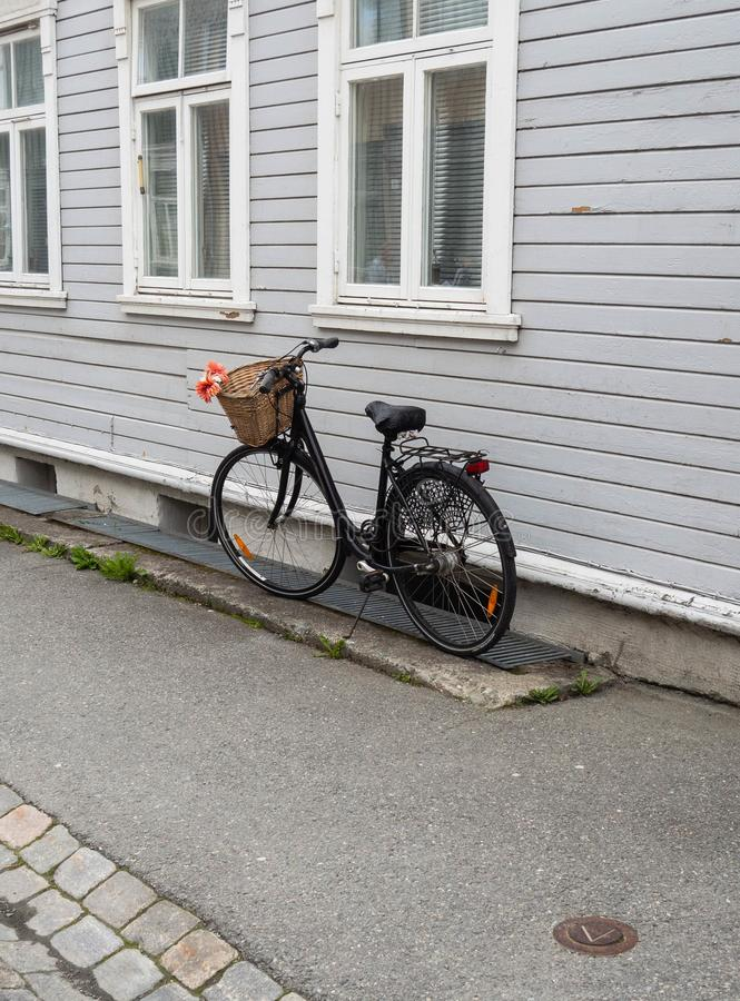 A black fashionable bicycle with a basket on the handlebars stands against the wall of an old wooden white house. On a paved sidewalk stock photography