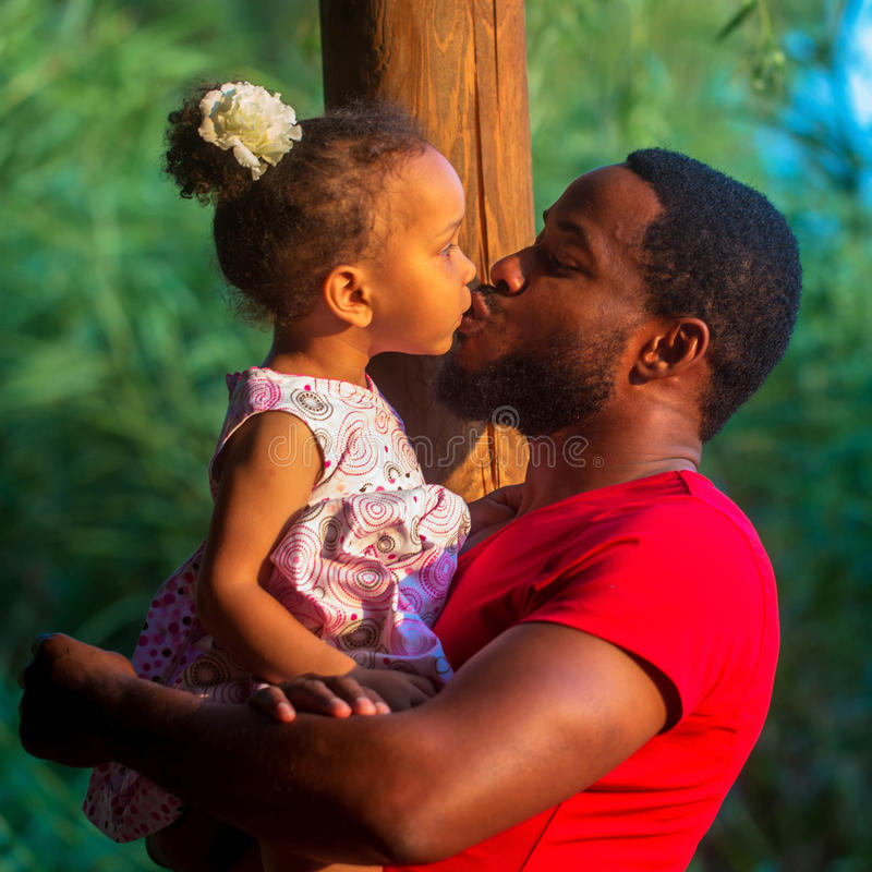 Black father kissing baby daughter. Happy family concept royalty free stock photo