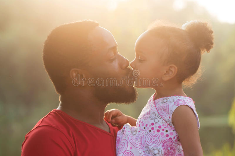 Black father kissing baby daughter. At sunset. Happy family concept royalty free stock photos