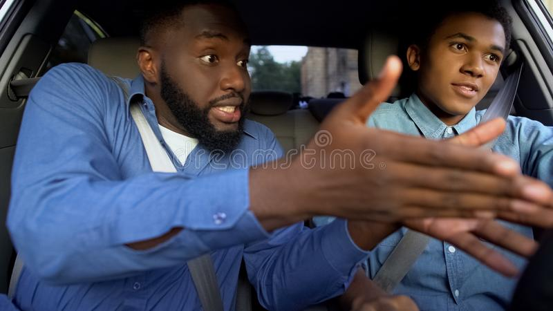 Black father and son arguing sitting car together, generations misunderstanding royalty free stock photo