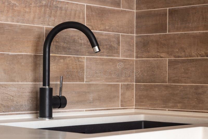 Black faucet, kitchen utensils, stone sink stock images