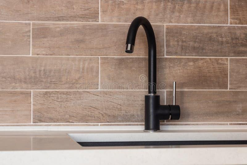 Black faucet, kitchen utensils, stone sink royalty free stock image