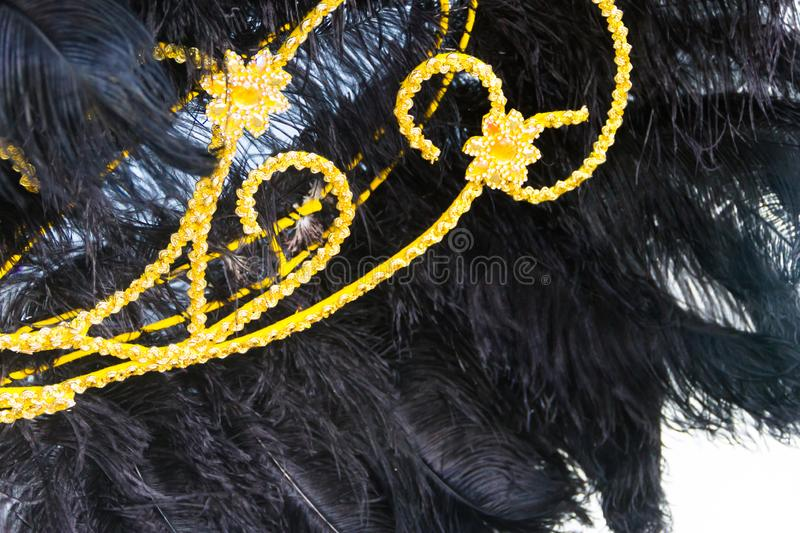 Detail of the helmet with feathers and embroidery for the carnival. Black feathers and golden embroidery of the backs for the carnival royalty free stock photography