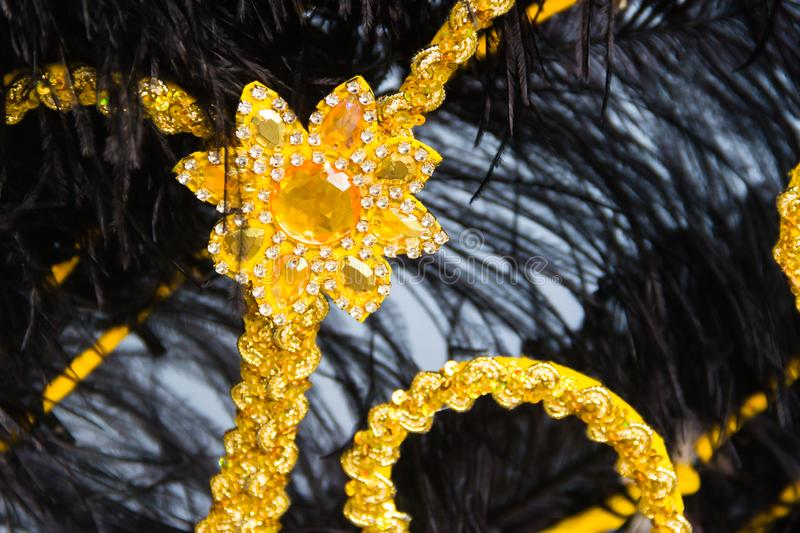 Detail of the helmet with feathers and embroidery for the carnival. Black feathers and golden embroidery of the backs for the carnival royalty free stock images
