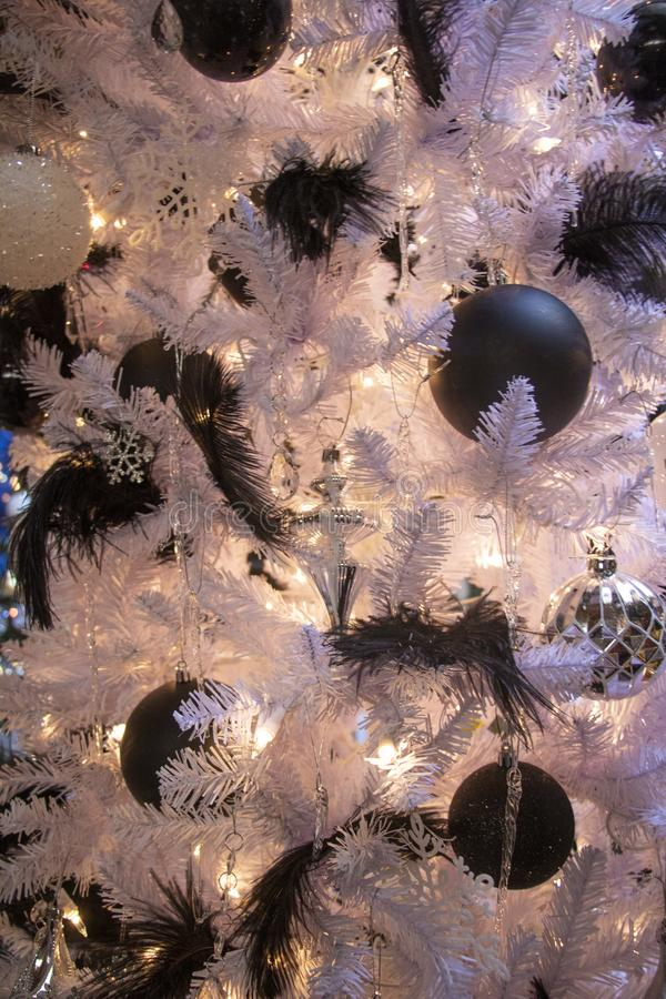 Black Feathers and Ornaments on a White Christmas Tree Close Up royalty free stock photography