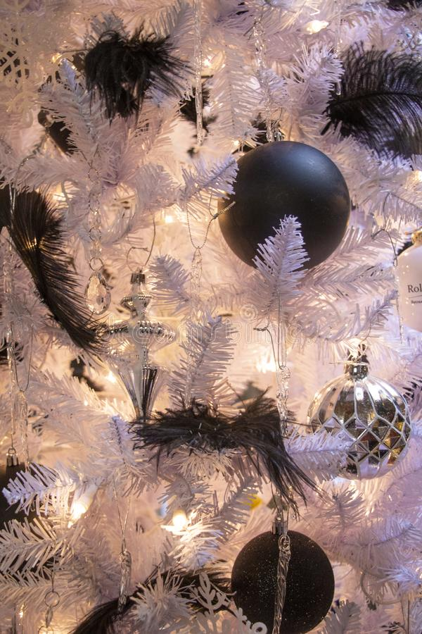 Black Feathers and Ornaments on a White Christmas Tree Close Up stock photo