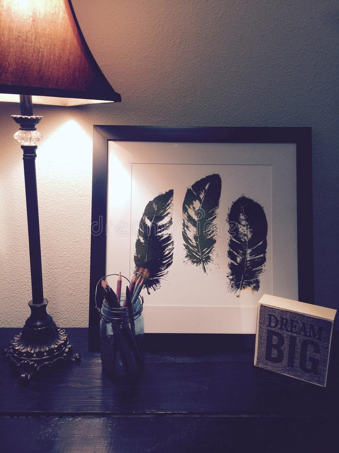 Black Feathers Painting Beside Brown and Black Lamp Shade royalty free stock photos