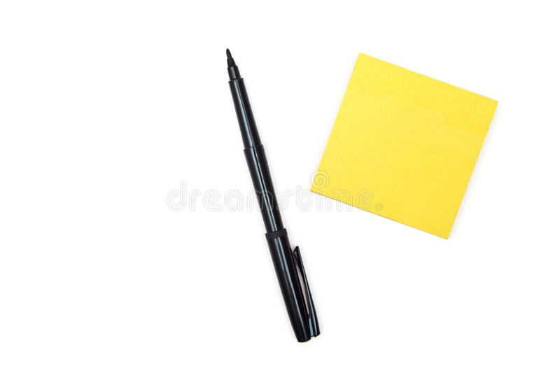 Black felt-tip pen near yellow sticky note. royalty free stock photo